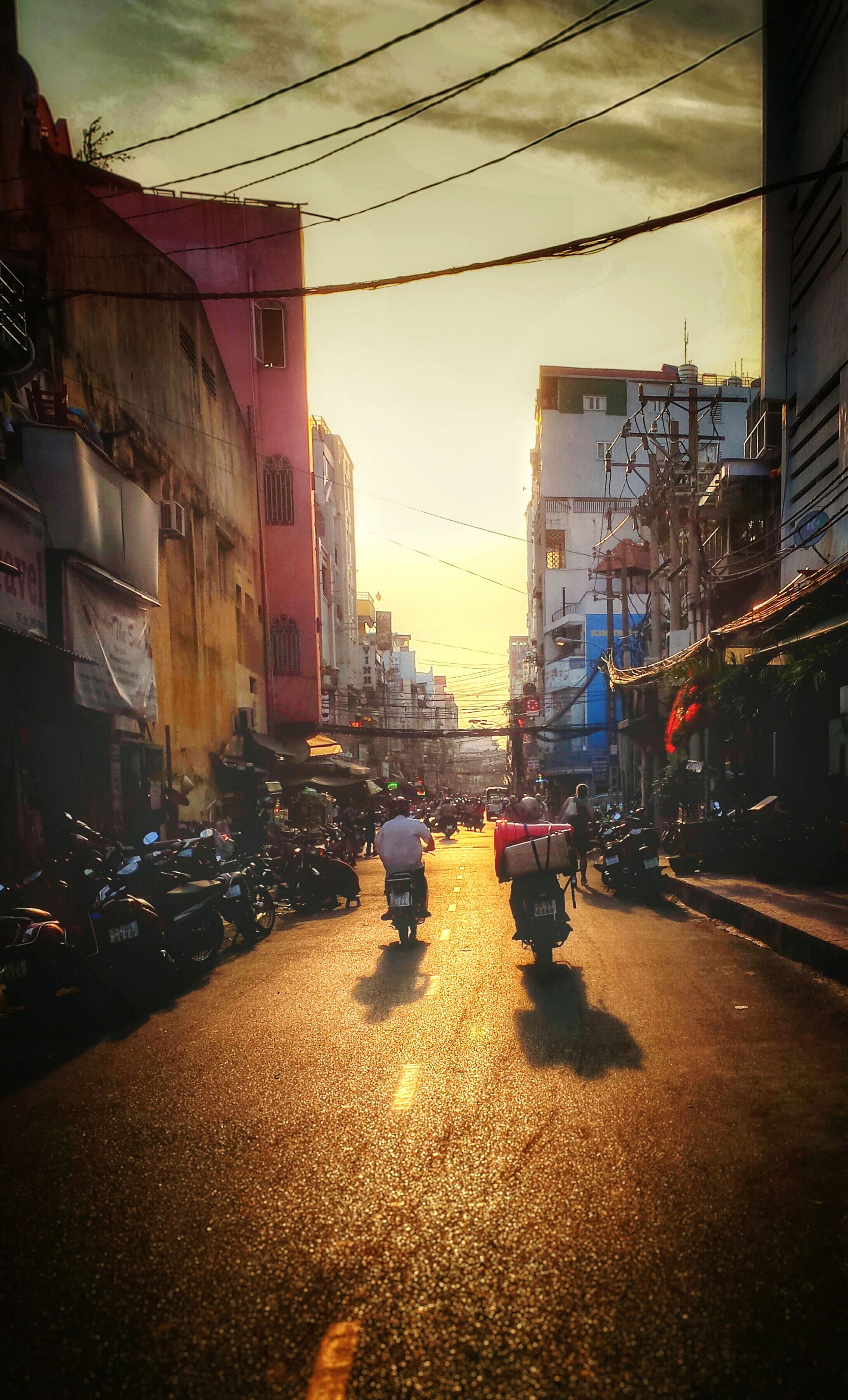 building exterior, transportation, architecture, street, car, built structure, city, land vehicle, mode of transport, city street, road, city life, sky, incidental people, building, traffic, residential structure, residential building, sunset, outdoors