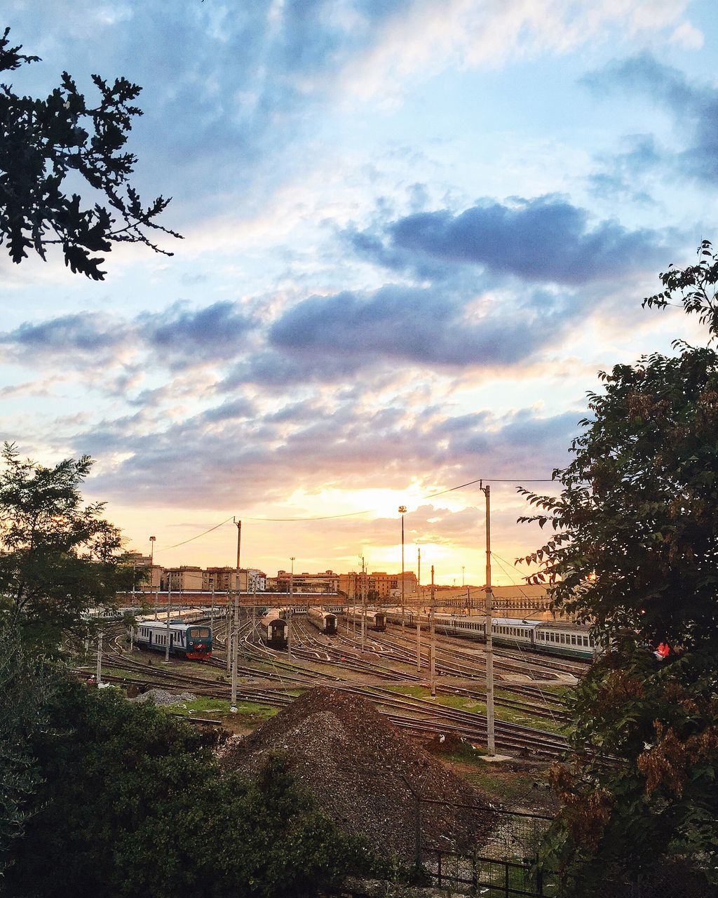 Trains At Shunting Yard Against Sky During Sunset