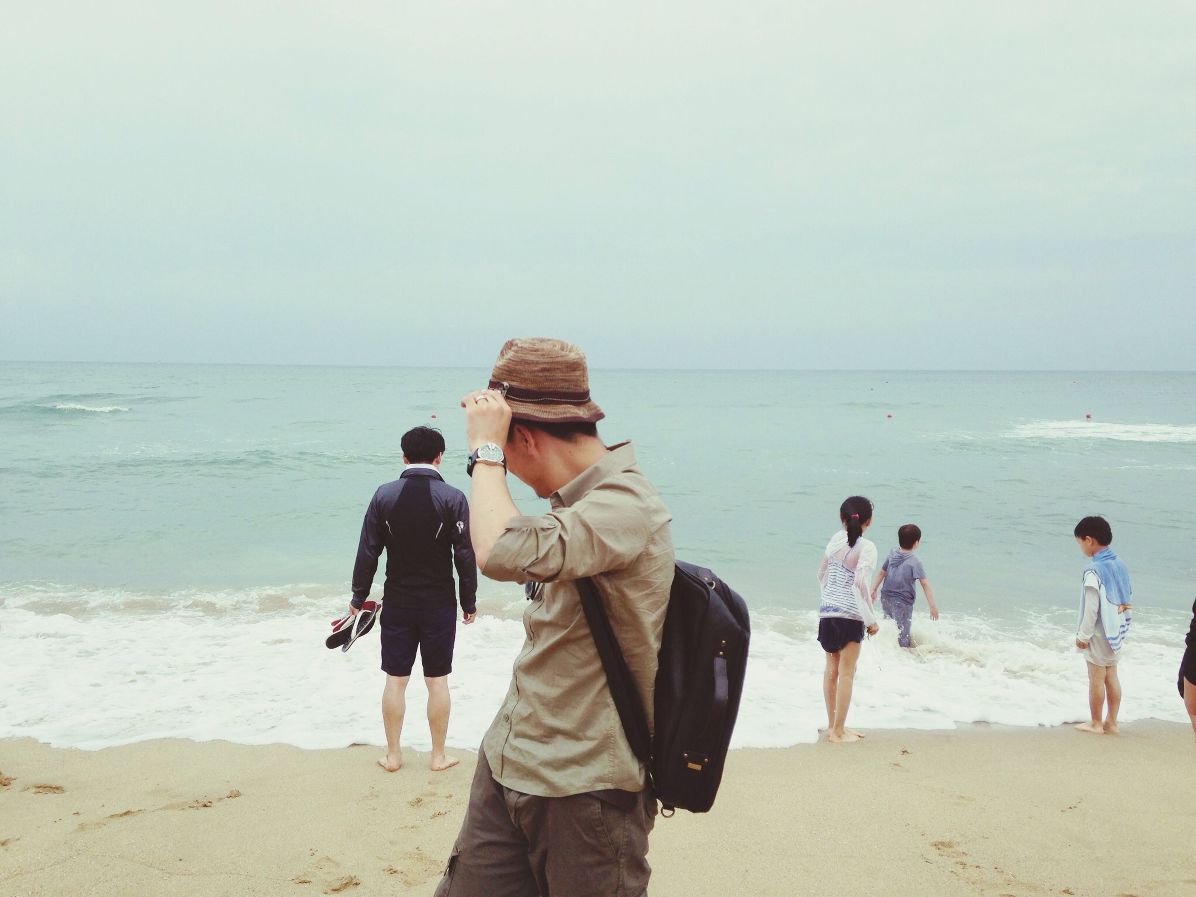 sea, horizon over water, beach, water, shore, lifestyles, leisure activity, sand, rear view, vacations, togetherness, clear sky, full length, standing, sky, men, wave, bonding