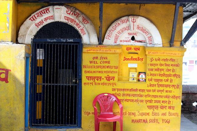 ASIA Building Exterior Communication Nepal Non-western Script Pashupatinath Red Chair Red Letters Text Travel Photography UNESCO World Heritage Site Yellow Wall Kathmandu