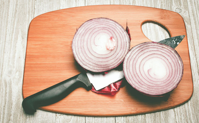 Sliced Not Diced - Overhead closeup of a red onion cut in half with a kitchen knife set on a wooden cutting board against a weathered wooden background Carving Board Carving Knife Closeup Cut Cutting Board Directly Above Food Food Preparation Freshness Garnish High Angle View Indoors  Kitchen Kitchen Knife Knife Onion Red Onion Sliced Sliced Onion Table Texture Vegetable Wood Wood - Material Wood Grain