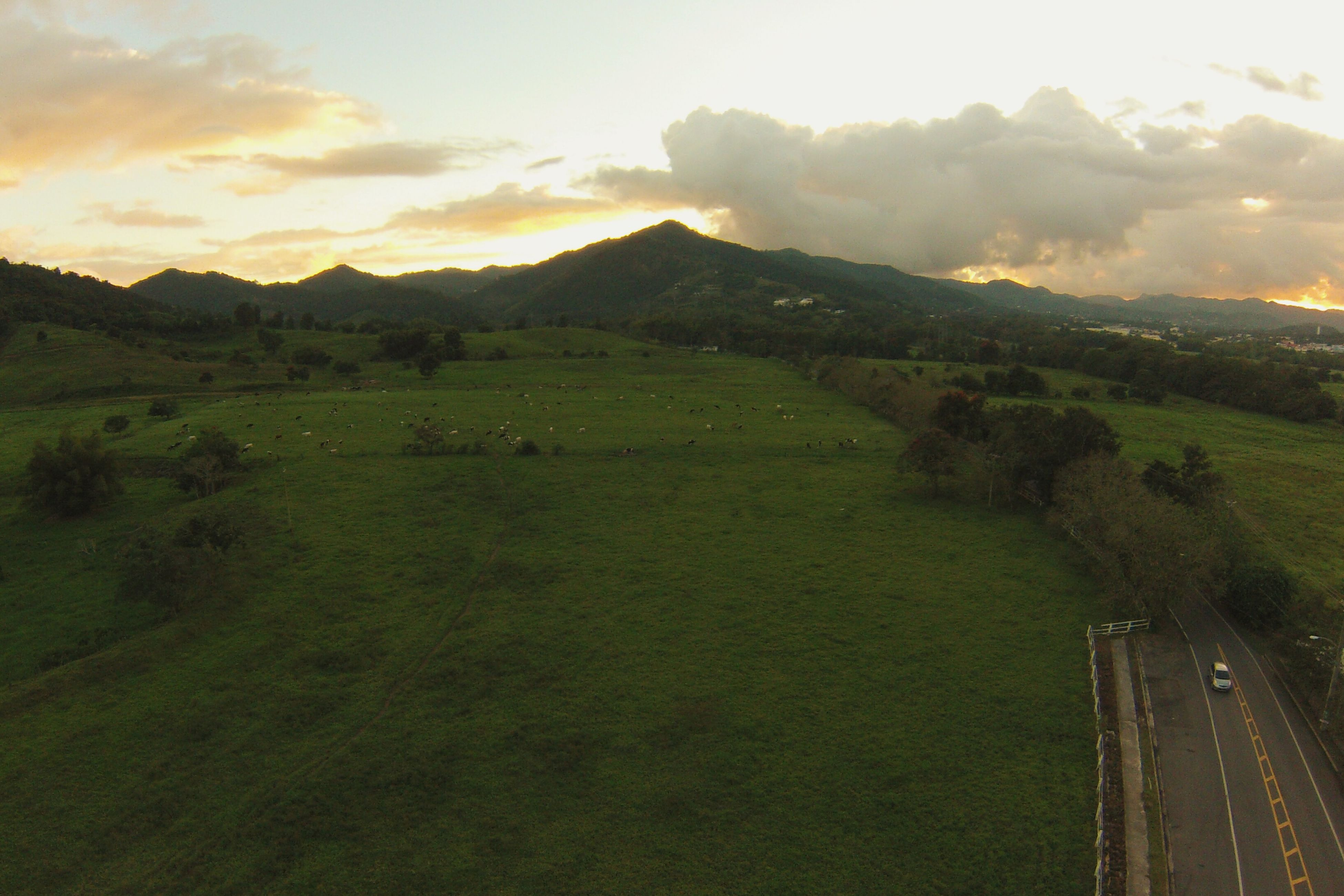mountain, landscape, tranquil scene, scenics, tranquility, beauty in nature, mountain range, sky, nature, grass, field, sunset, idyllic, non-urban scene, green color, rural scene, hill, tree, remote, cloud - sky