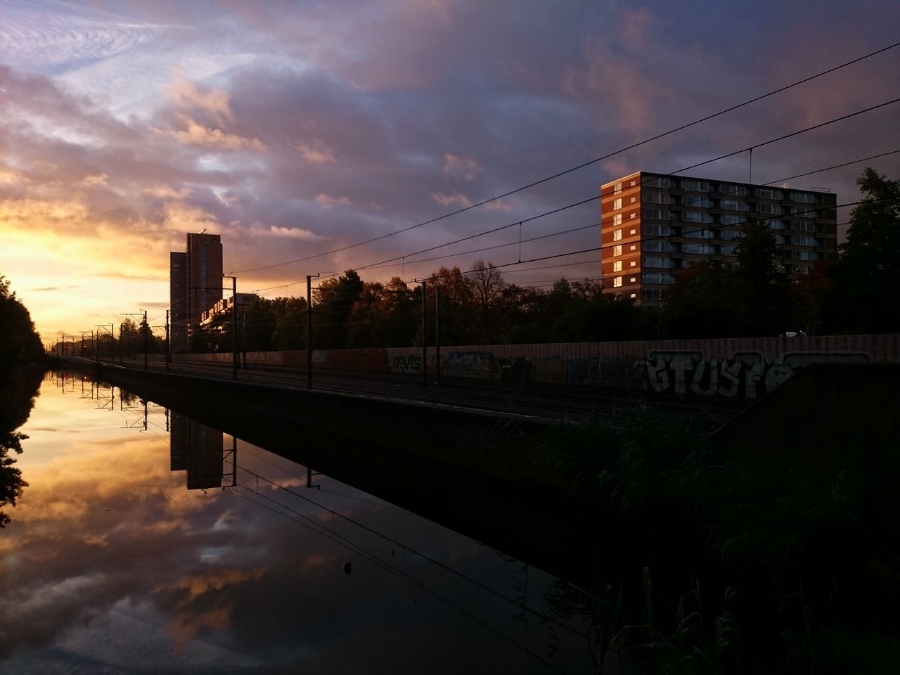 sunset, sky, cloud - sky, reflection, architecture, dusk, built structure, water, tree, outdoors, nature, no people, cable, transportation, building exterior, city, beauty in nature, day