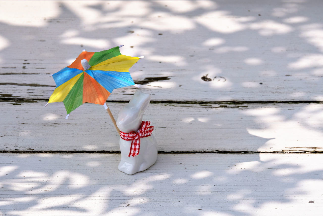 Animal Themes Beauty In Nature Easter Figurine  Happy Easter Isolated Color Multi Colored Multicolored Sunshade Multicolored Umbrella No People Old Bench Outdoors Porcelain Rabbit Rabbit Rabbit Figurine Red Ribbon Reflections Sunprotection Sunshade Sunshine Umbrella White Bench