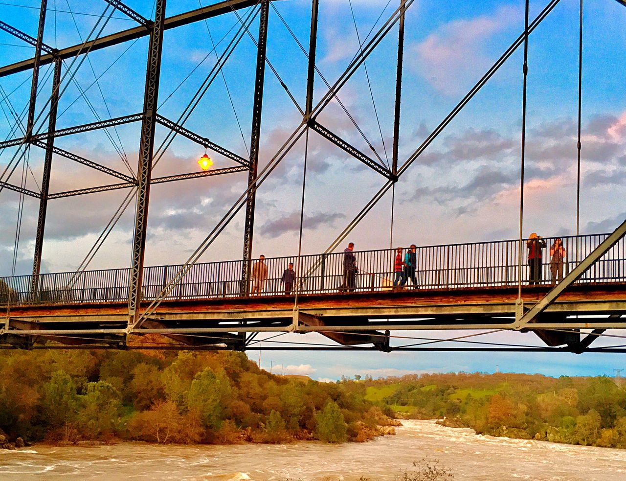bridge - man made structure, connection, architecture, sky, transportation, engineering, built structure, suspension bridge, bridge, river, cloud - sky, day, water, road, outdoors, blue, city, tree, nature, no people