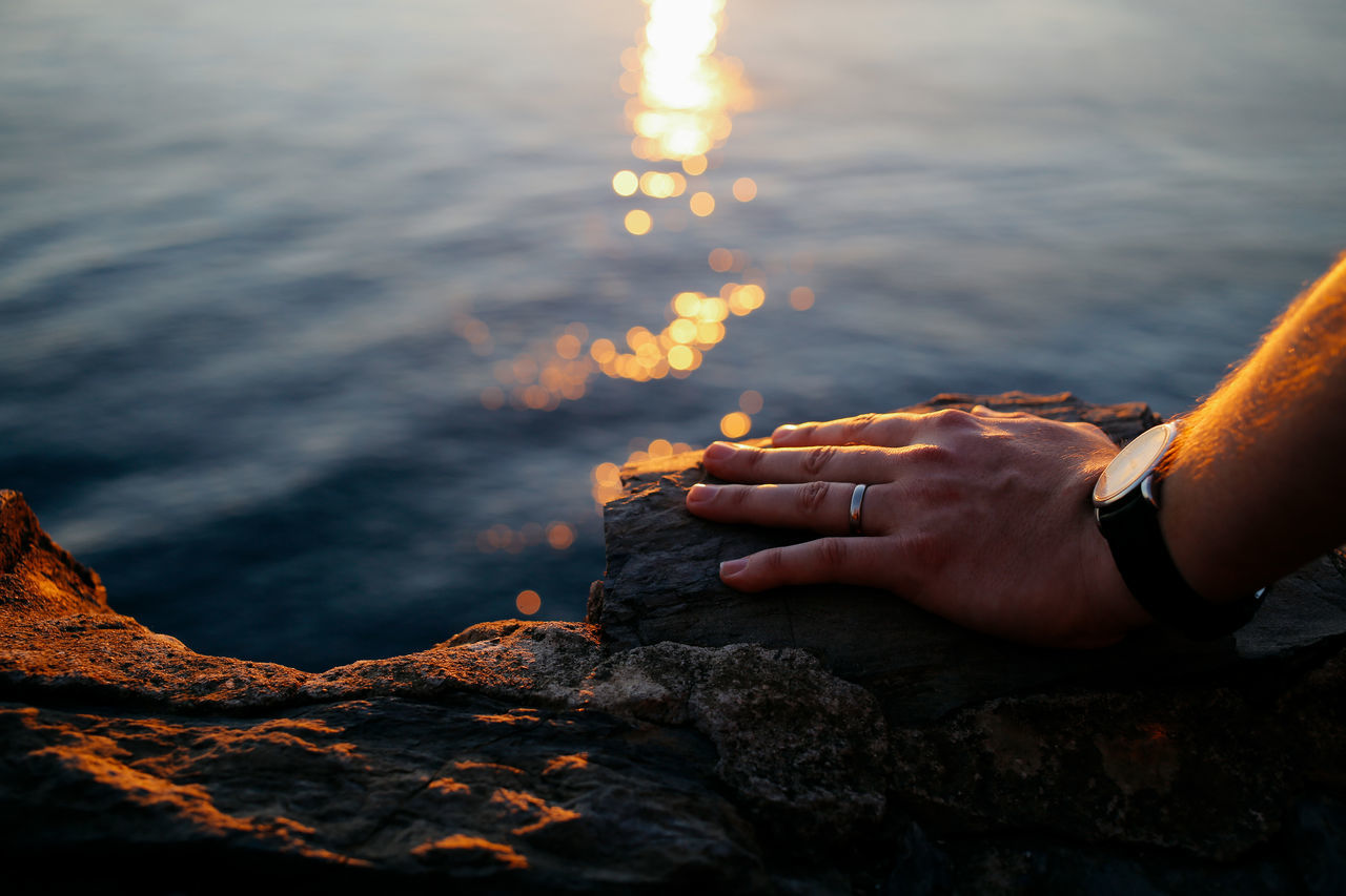 Watching the sunset Bokeh Close-up Human Hand Igniting Light Reflection Man Married One Man Only One Person Outdoors Rock Sea Sunset Tranquility Watch Watching The Sea Watching The Sunset Water Wedding Band Wedding Ring