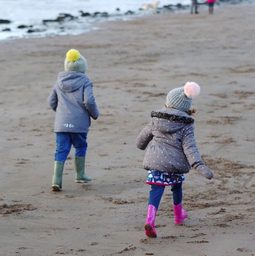 Childhood Full Length Child Casual Clothing Rear View Sand Beach Males  Children Only Playing Two People Outdoors Real People Sand Pail And Shovel Day People Togetherness Running Kids Being Kids Race Bobble Hat
