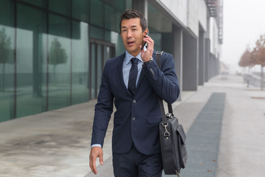 Successful Asian businessman using mobile technology. Answering Architecture Building Exterior Business Businessman Communication Connection Corporate Business Day Focus On Foreground Front View Full Suit Mature Men Men Mobile Phone One Person Outdoors Portable Information Device Real People Suit Talking Technology Using Phone Well-dressed Wireless Technology