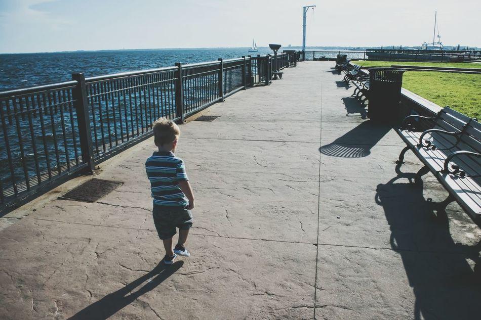 Leading The Way Boy Walking Independent  Childhood Long Walk Walking Pier Walkway Memory Lane Going Forward  Being Independent Being Adventurous Growing Up Ocean Walkway Lines The City Light