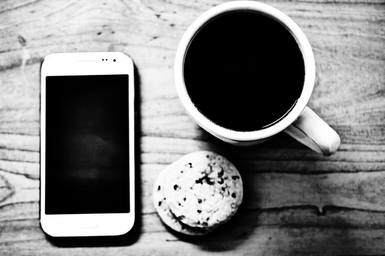 Directly Above View Of Coffee Cup With Cookies By Mobile Phone On Table