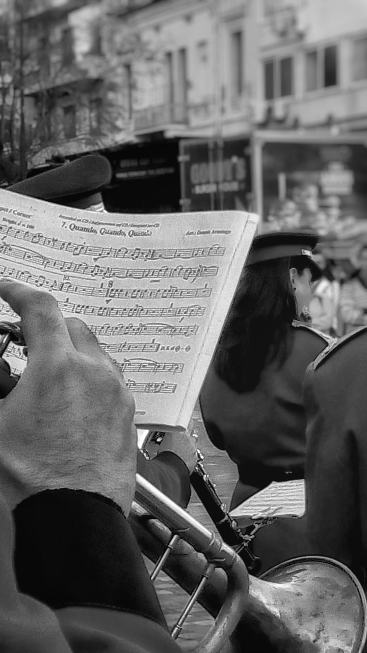 music, musician, musical instrument, playing, real people, performance, arts culture and entertainment, holding, sheet music, skill, men, two people, human hand, focus on foreground, musical note, togetherness, day, lifestyles, outdoors, classical music, wind instrument, plucking an instrument, close-up, people