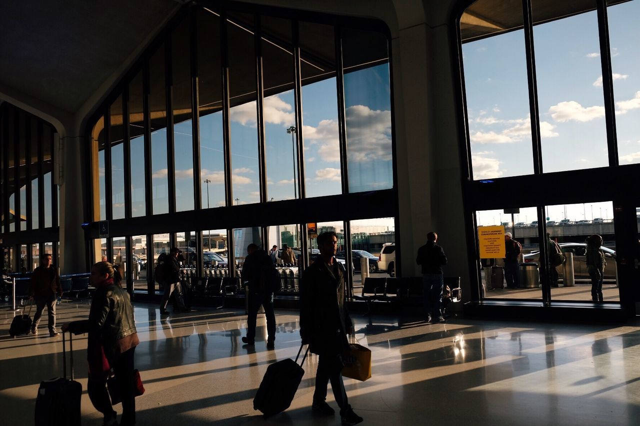 airport, men, indoors, real people, travel, large group of people, transportation, window, architecture, transportation building - type of building, public transportation, built structure, luggage, railroad station, women, lifestyles, group of people, journey, day, sky, airport departure area, standing, modern, city, people