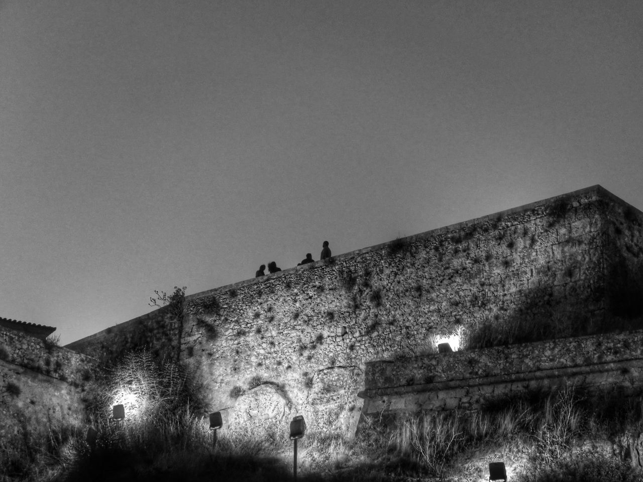 Architecture Black & White Building Exterior Built Structure Castle Castle Walls Clear Sky Damaged Dark Day Group Of People High Section Incidental People Low Angle View Monochrome Photography Night Sky Outdoors Overnight Success Peaceful Sky Solitude Tranquil Scene Tranquility Unrecognizable Person Weathered