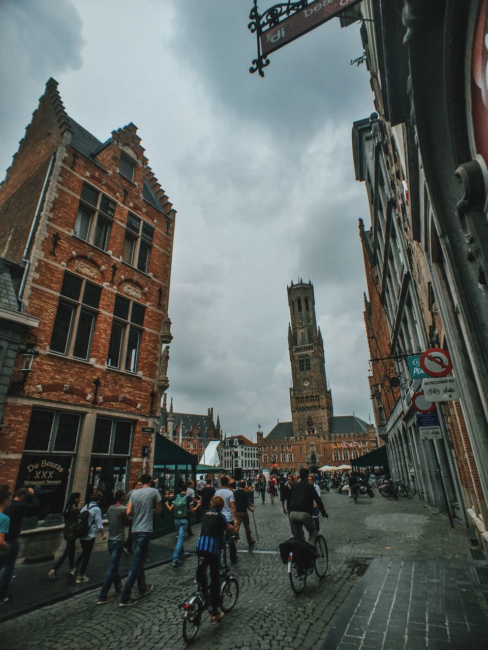 architecture, building exterior, built structure, real people, street, bicycle, sky, cloud - sky, land vehicle, large group of people, city, men, transportation, outdoors, road, lifestyles, women, day, group of people, people