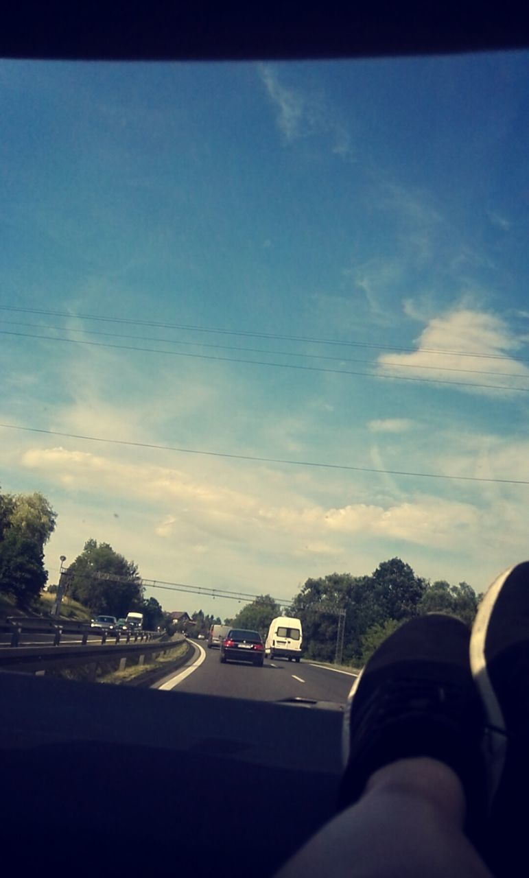 sky, transportation, car, human body part, road, car interior, cloud - sky, land vehicle, human hand, one person, day, car point of view, men, real people, tree, nature, close-up, indoors, people