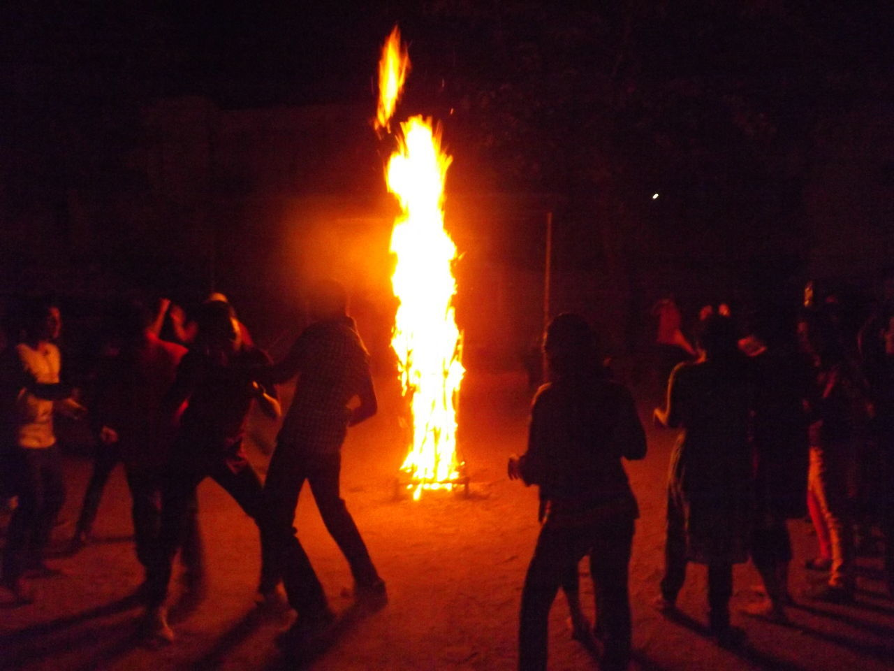 burning, flame, real people, night, men, heat - temperature, medium group of people, leisure activity, outdoors, women, bonfire, event, celebration, arts culture and entertainment, standing, lifestyles, performance, togetherness, crowd, period costume, people