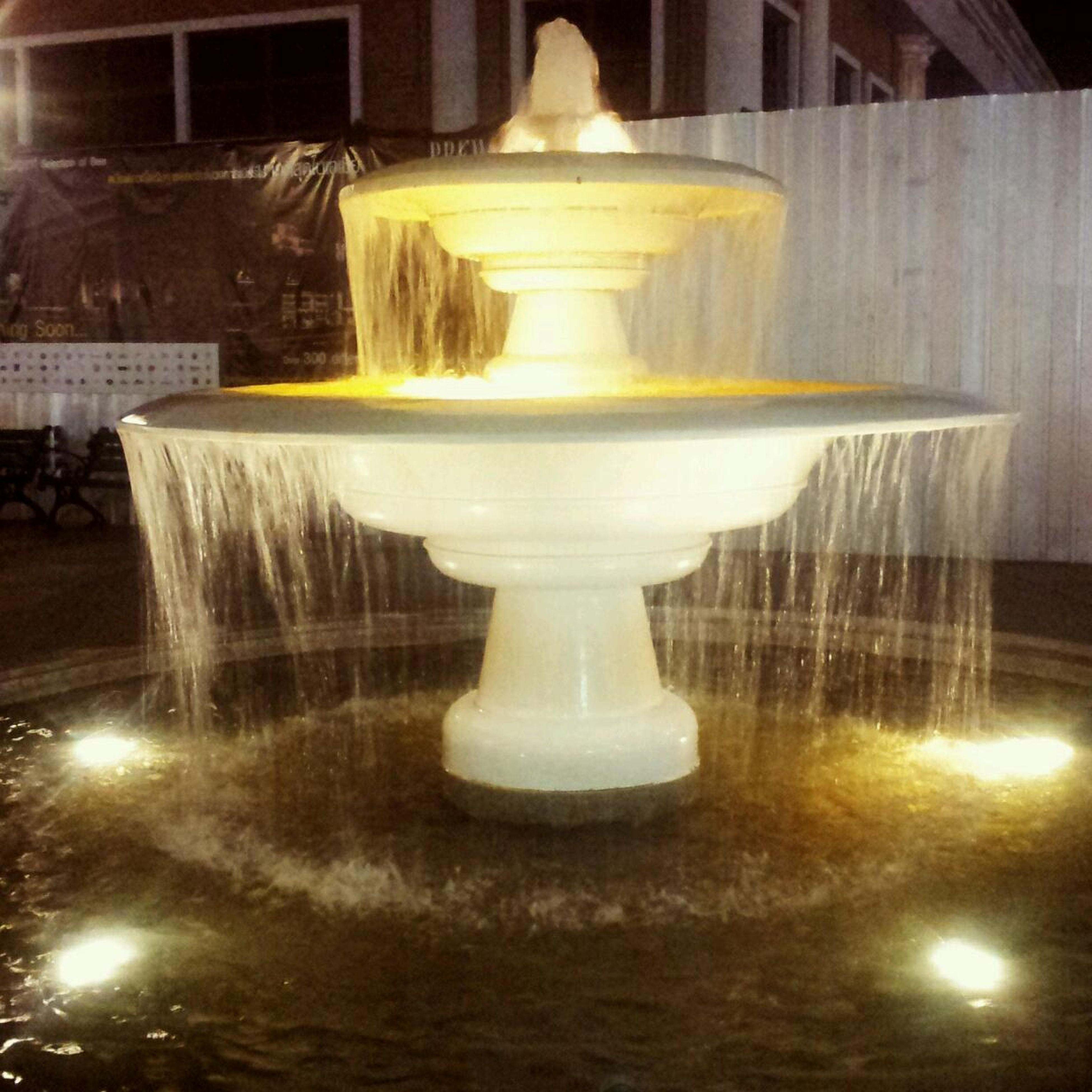 illuminated, indoors, reflection, fountain, water, lighting equipment, night, glowing, motion, lit, light - natural phenomenon, no people, religion, candle, spirituality, waterfront, in a row, art and craft, splashing, long exposure