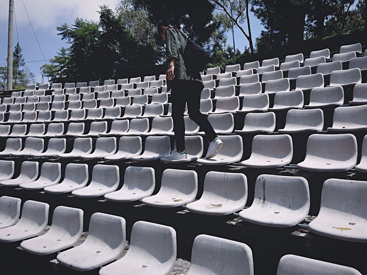 in a row, seat, one person, chair, empty, leisure activity, standing, large group of objects, day, outdoors, audience, real people, stadium, tree, one man only, auditorium, only men, people