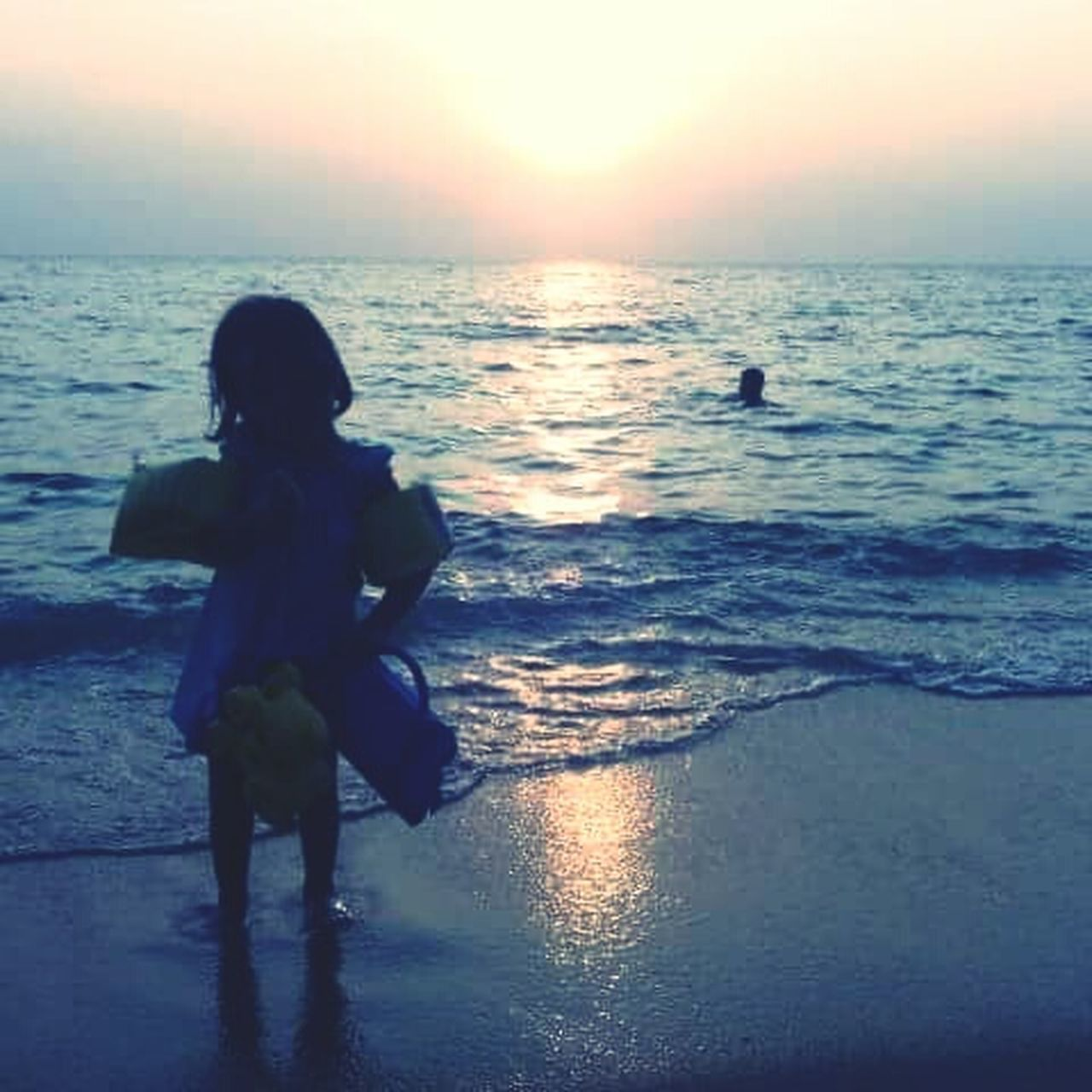 sea, water, beach, real people, sunset, full length, rear view, leisure activity, one person, horizon over water, lifestyles, reflection, nature, walking, beauty in nature, childhood, standing, sand, outdoors, scenics, vacations, ankle deep in water, sky, wave, day, people