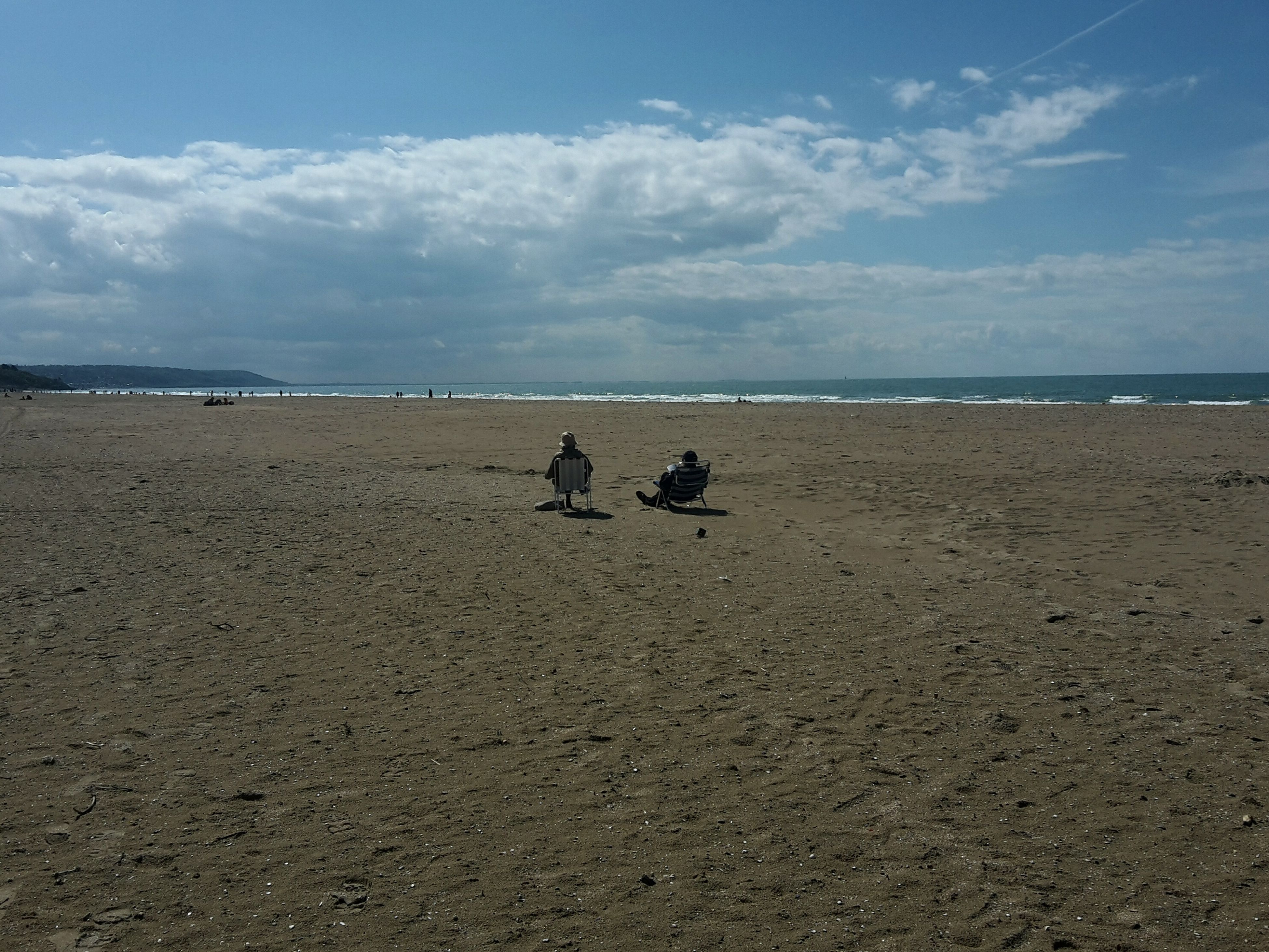 beach, sky, sea, water, cloud - sky, horizon over water, shore, tranquil scene, tranquility, scenics, nature, cloud, beauty in nature, mammal, day, cloudy, outdoors, lifestyles, vacations, unrecognizable person, idyllic, coastline, remote, blue, non-urban scene