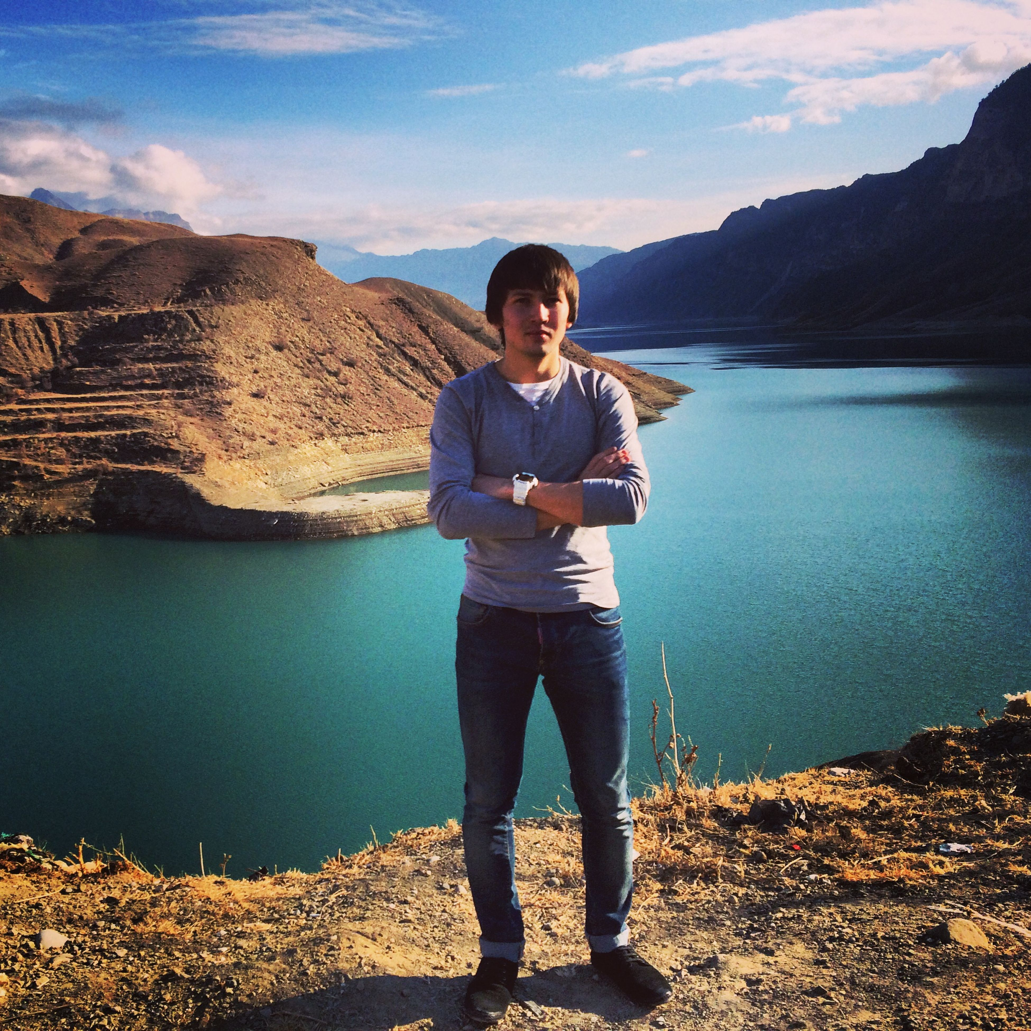 lifestyles, casual clothing, water, leisure activity, standing, young adult, full length, person, portrait, looking at camera, sky, mountain, young men, front view, sunglasses, rock - object, three quarter length