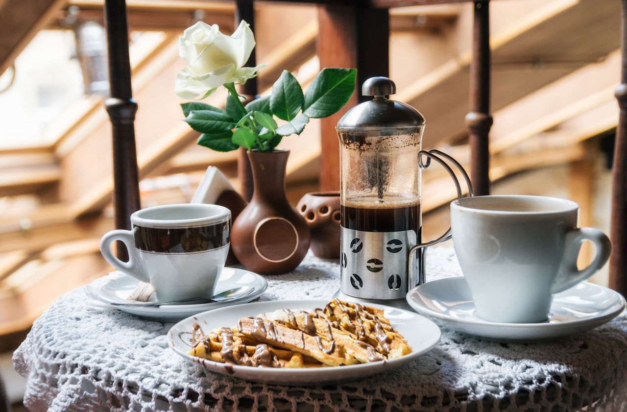 Two cup of coffee and waffles with chocolate. Tasty and traditional breakfast. Breakfast Cappuccino Chocolate Close-up Coffee - Drink Coffee Cup Cup Day Food Food And Drink Freshness Heat - Temperature Indoors  No People Rose - Flower Table Tasty Waffle