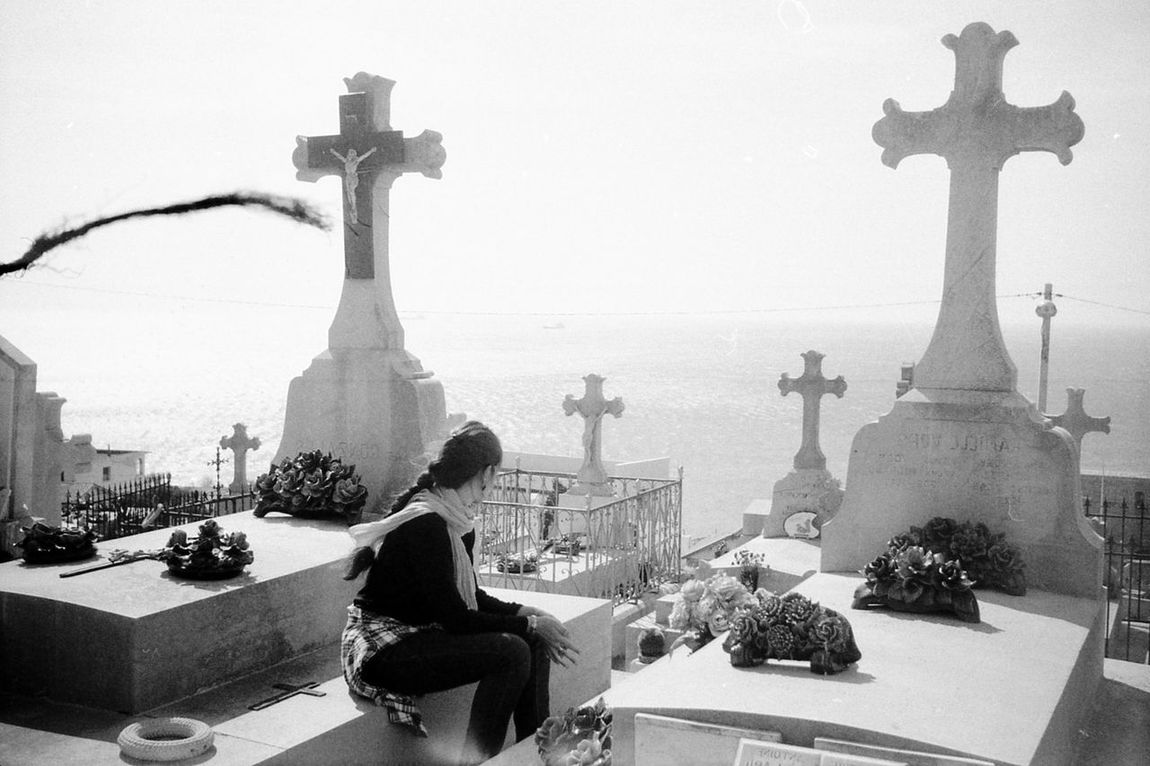 Cemetary Sète girl watching the sea black and white argentique Cross Spirituality film photography 35mm Filmphotography 35mm Film Romantic Scenery Blackandwhite Nofilter Cemetery Photography Seascape SETE Girl From Behind Watching The Sea