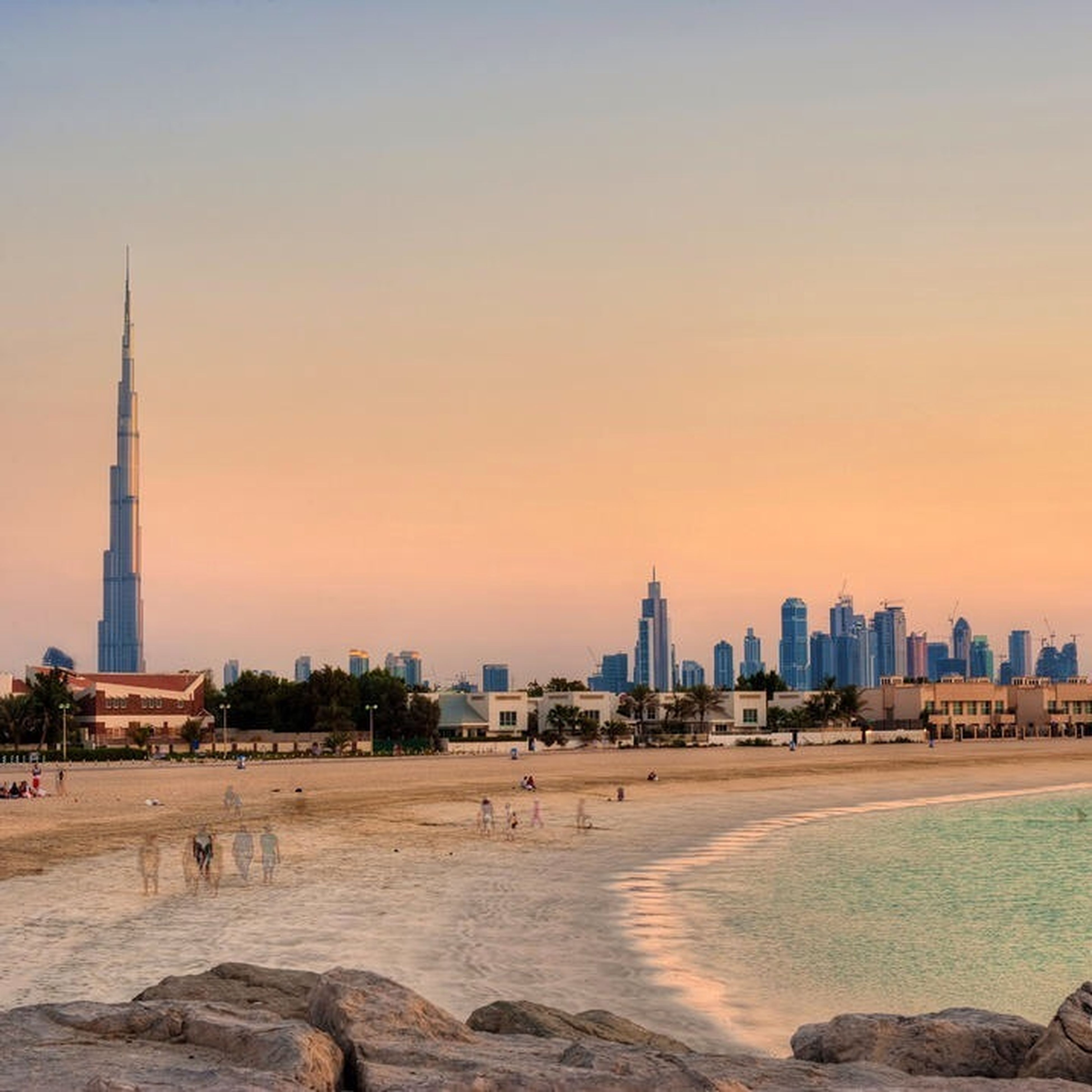 architecture, building exterior, built structure, city, tower, tall - high, famous place, international landmark, travel destinations, skyscraper, tourism, clear sky, capital cities, beach, cityscape, sunset, travel, sea, copy space, water