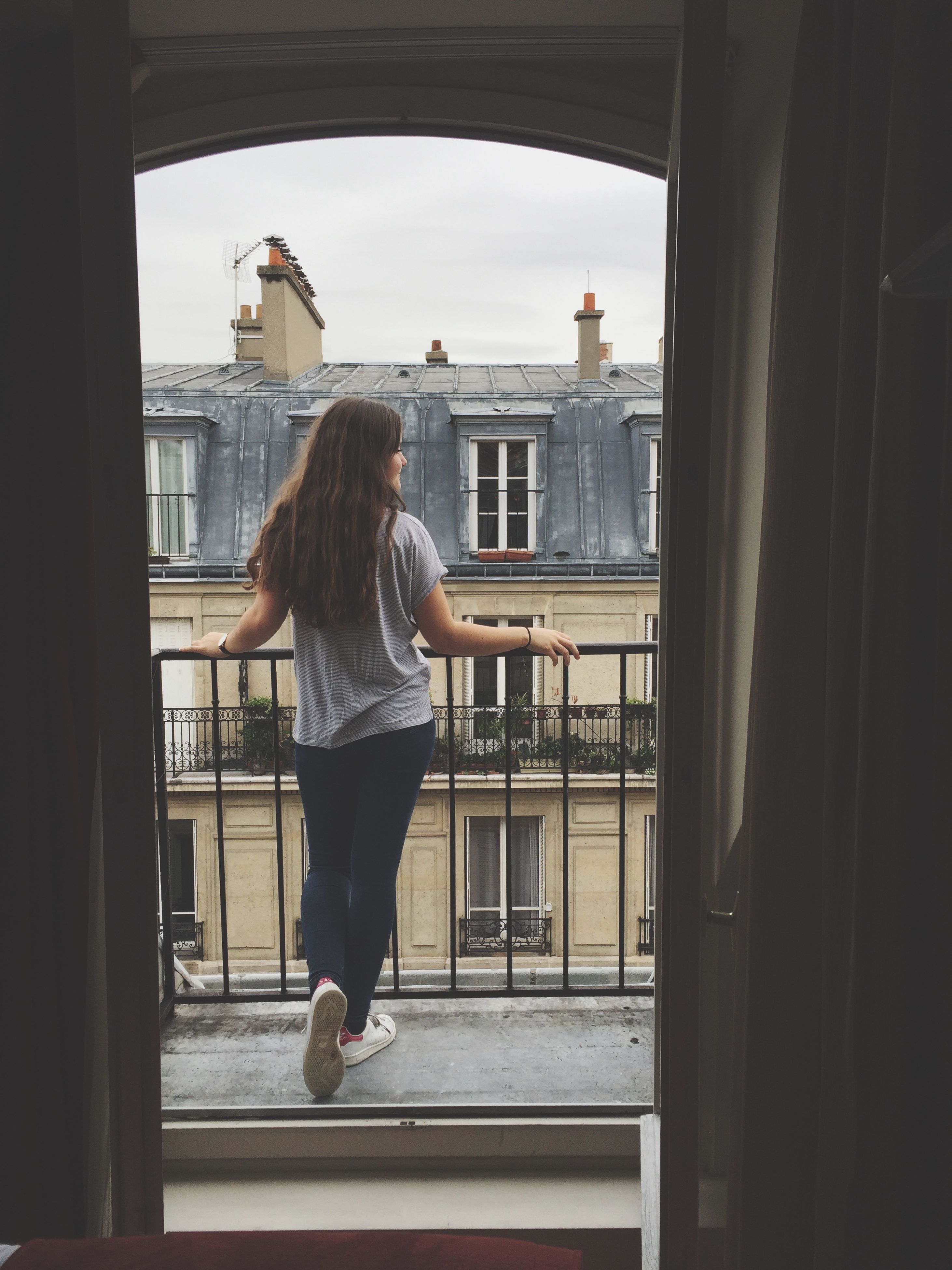 full length, lifestyles, casual clothing, window, standing, leisure activity, indoors, rear view, architecture, built structure, young adult, person, building exterior, three quarter length, side view, house, holding, day