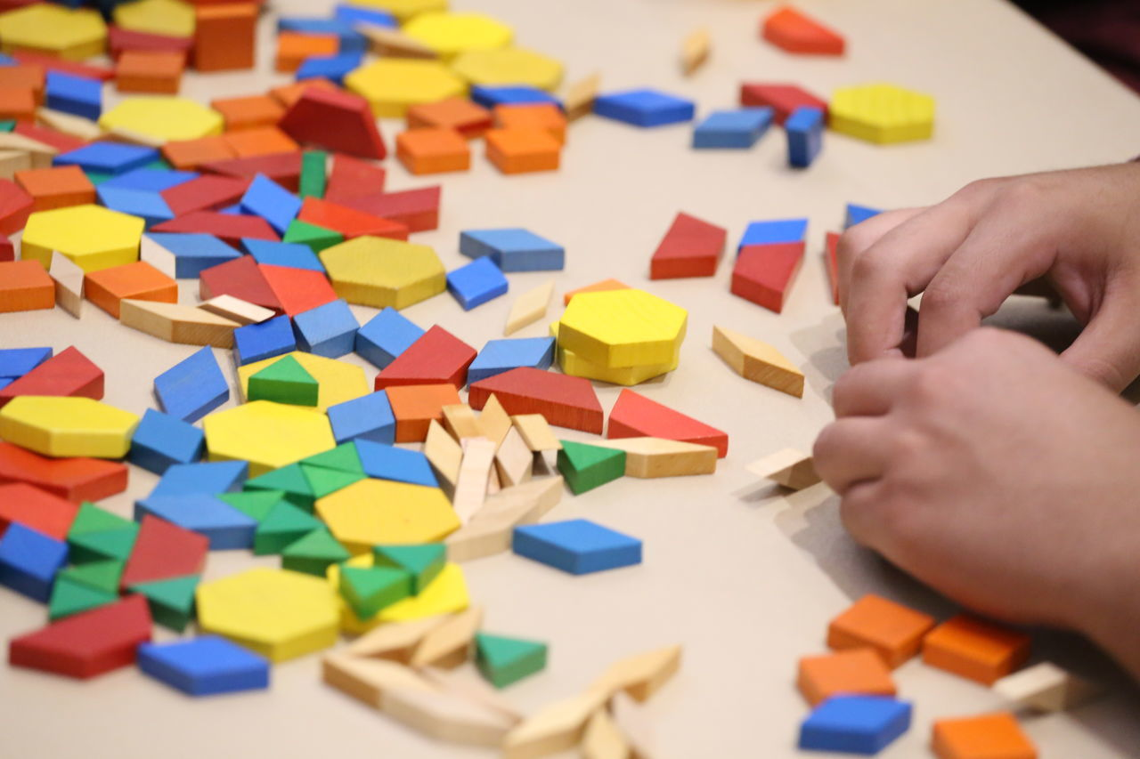 multi colored, human hand, human body part, puzzle, creativity, childhood, indoors, real people, toy, leisure activity, large group of objects, human finger, one person, toy block, table, leisure games, lifestyles, close-up, day, people