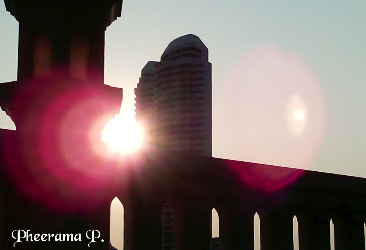 sun, lens flare, architecture, built structure, building exterior, sunbeam, sunlight, outdoors, sky, no people, sunset, low angle view, skyscraper, clear sky, day, illuminated, city, nature