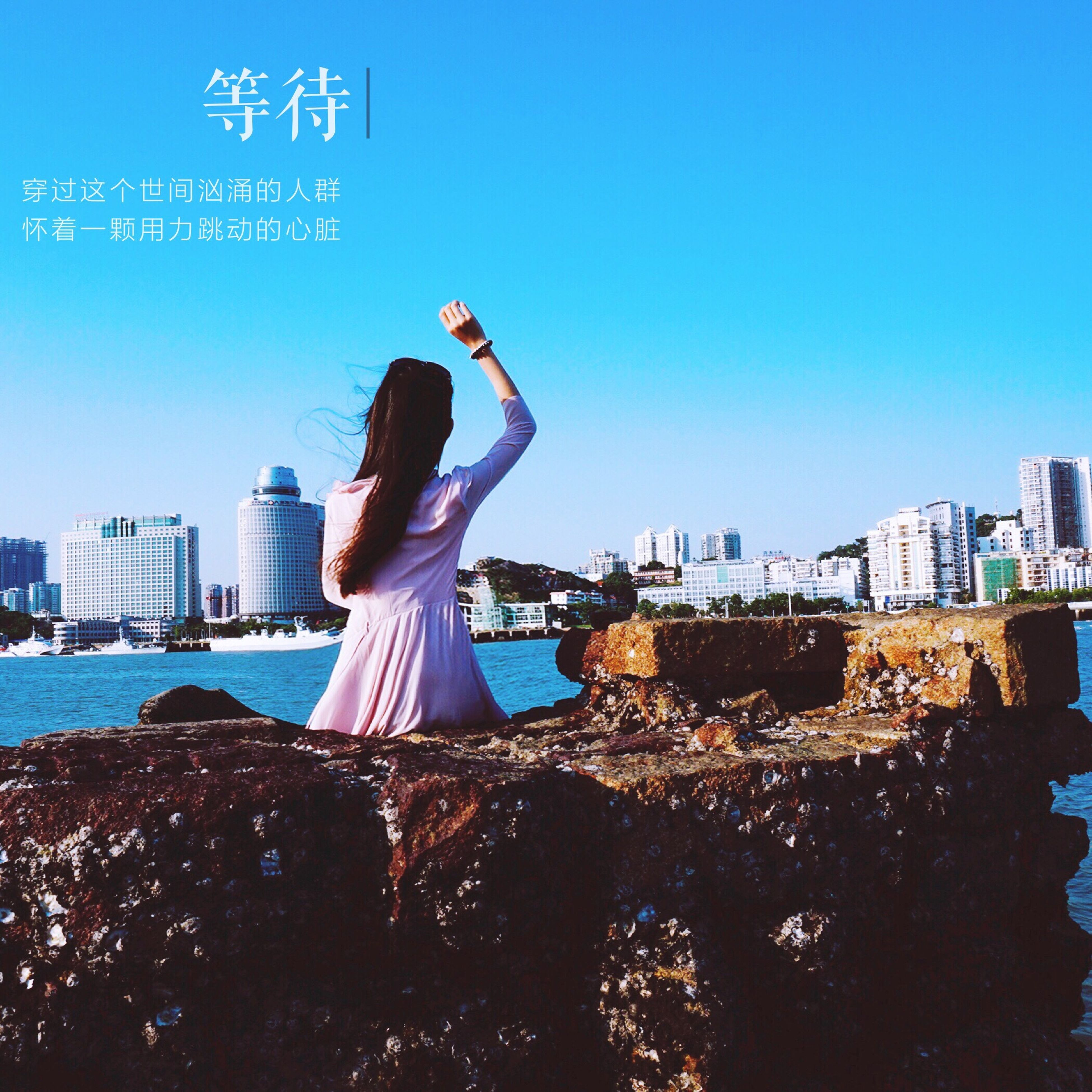real people, clear sky, rear view, one person, architecture, built structure, building exterior, outdoors, standing, city, cityscape, day, skyscraper, sky, blue, leisure activity, women, full length, modern, sea, urban skyline, young adult, adult, people
