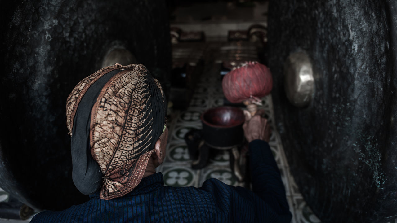 Rear View Of Man Hitting Gong In Temple