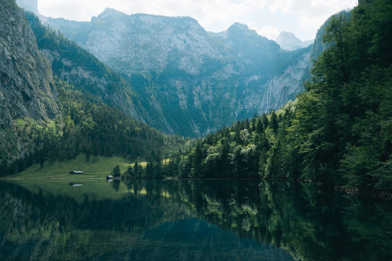 Reflection in a mountain lake with forest against sky