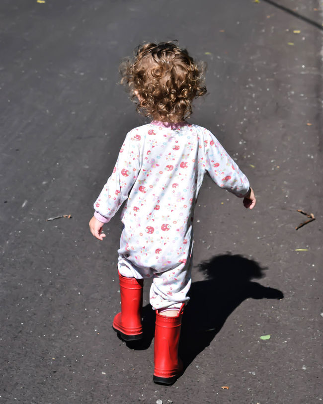 Little Girl Walking Childhood Full Length High Angle View Leisure Activity Little Girl Nature Outdoors Rear View Red Boots Road Standing Strong Shadow Walking