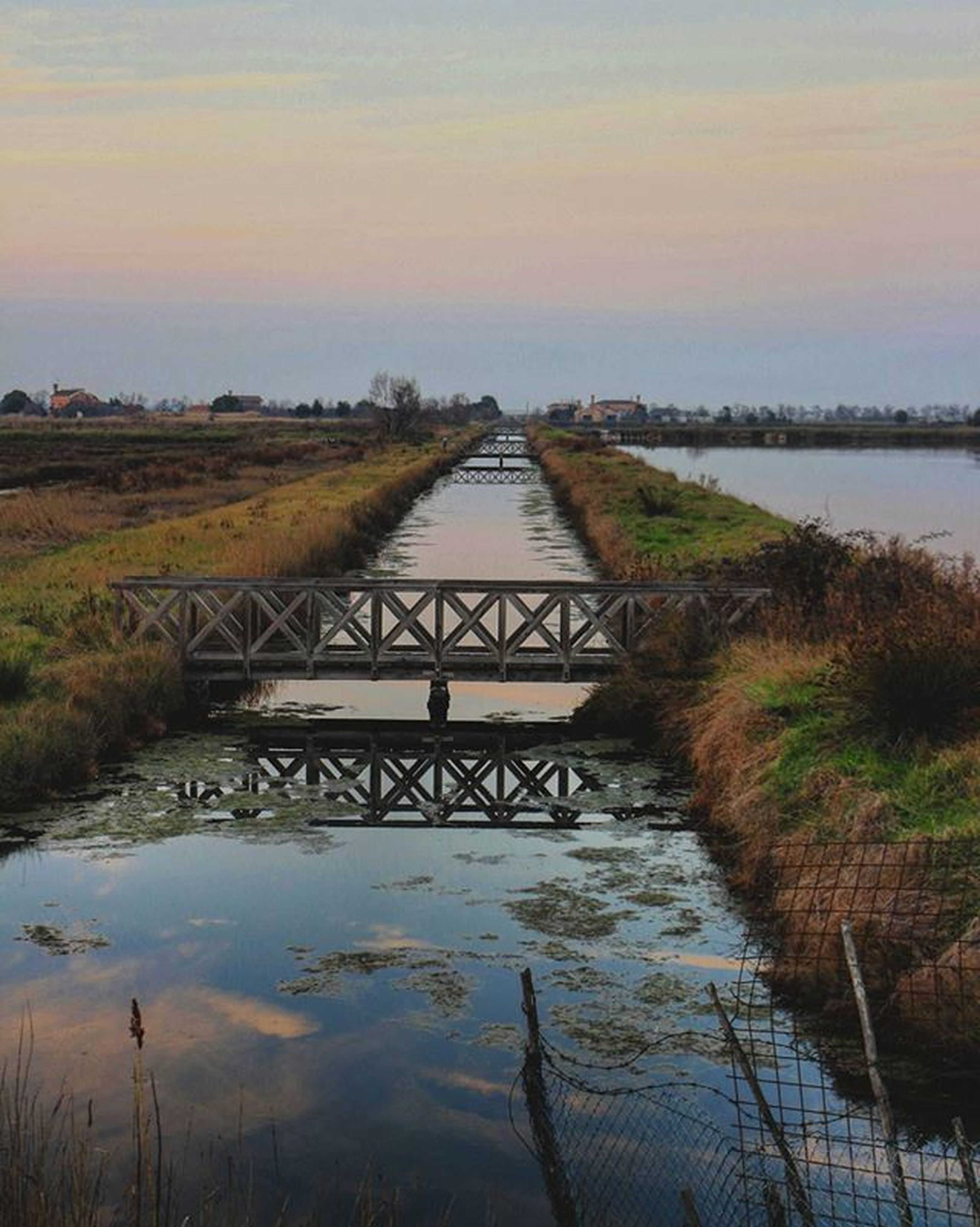 water, sunset, reflection, connection, tranquility, built structure, tranquil scene, river, sky, lake, bridge - man made structure, architecture, scenics, nature, beauty in nature, plant, no people, grass, bridge, landscape