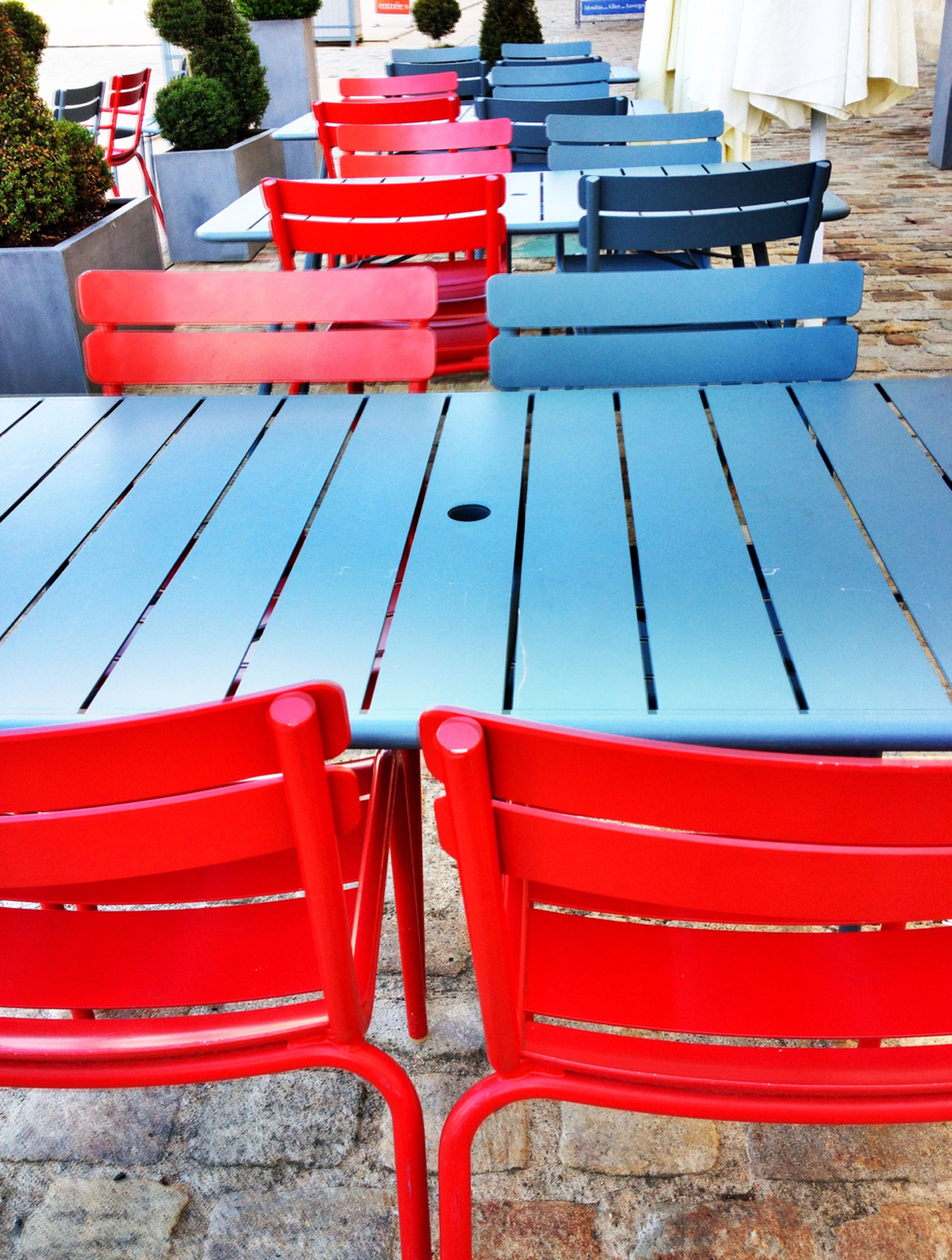 red, chair, empty, seat, absence, in a row, bench, day, outdoors, no people, transportation, railing, sunlight, high angle view, water, furniture, metal, group of objects, relaxation, table