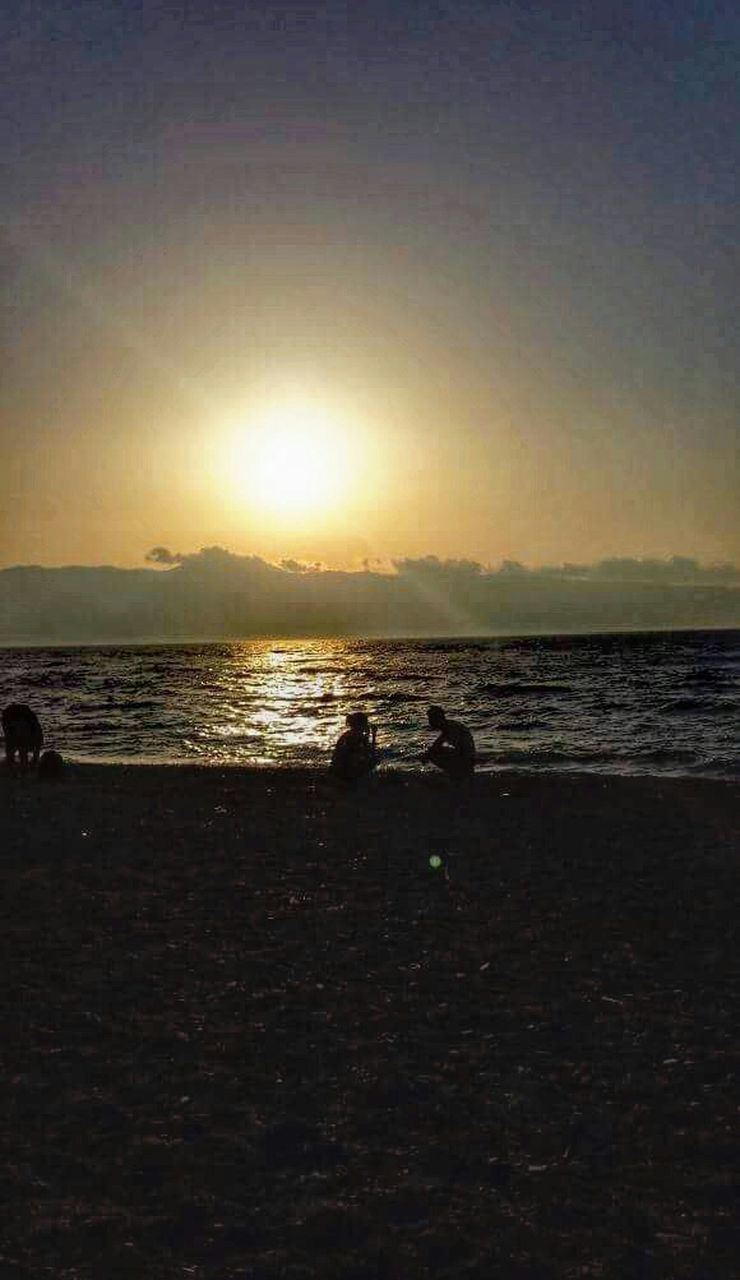 sea, sunset, silhouette, beach, water, nature, sky, scenics, horizon over water, tranquility, tranquil scene, sun, beauty in nature, outdoors, leisure activity, real people, clear sky, togetherness, vacations, leisure, wave, day