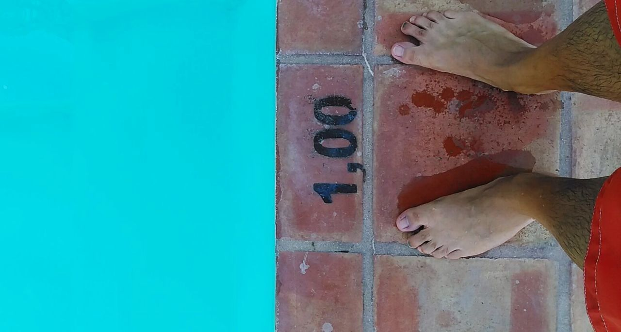 Low Section Of Man Standing By Number On Pool Side