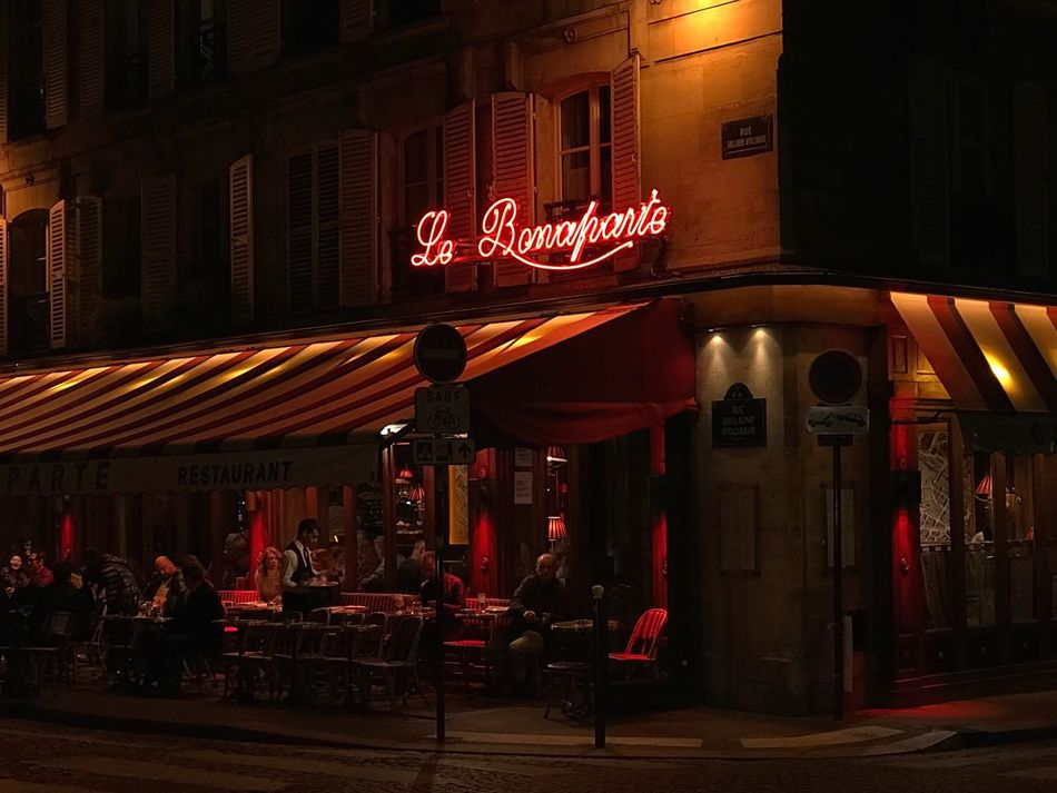 Night Illuminated Neon Nightlife City Cafe Restaurant Streetphotography Night Lights French Lifestyle French Food Parisian ParisianLifestyle Red Waiter People Pavement Chairs Tables Windows Shutters Stripes Quartier Latin Saint Germain Des Pres Paris