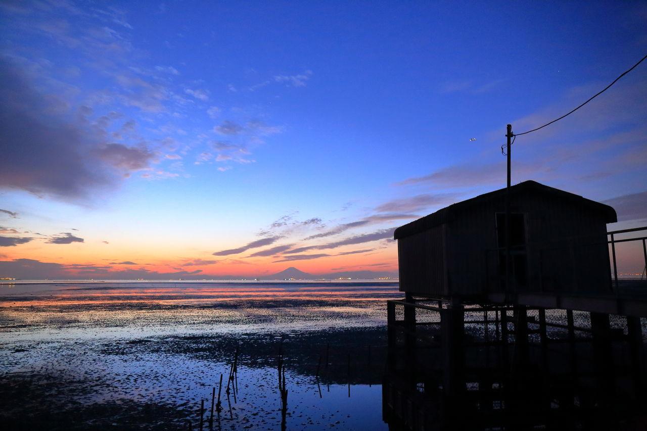 Stilt House On River Against Sky At Sunset