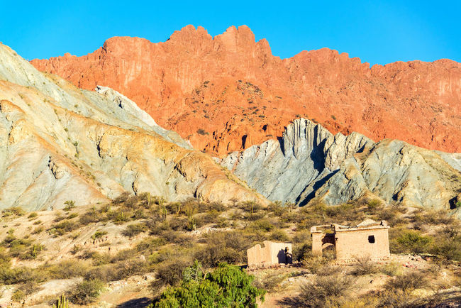 A ruined building at the base of dramatic colorful hills in the small town of Quiriza near Tupiza, Bolivia Andean Andes Beauty Bolivia Cactus Canyon Color Colorful Country Countryside Desert Destination Formation Full Hills Landscape Mountains Nature Rock Rocks Ruined South America Travel TUPIZA Valley