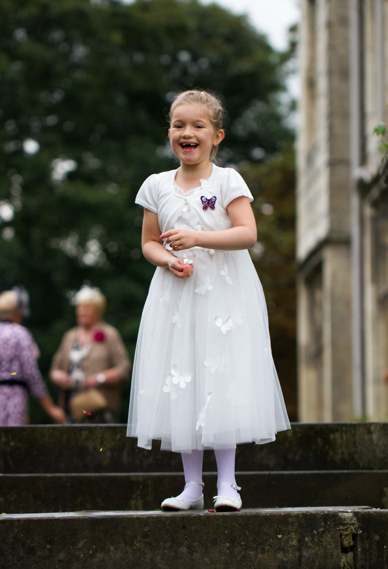 A young girl in a bridesmaid dress laughing and smiling at a wedding venue. Bridesmaid Bridesmaid Dress Bridesmaids Childhood Children Children Photography Children Playing Children's Portraits Flower Girl Full Length Girl Happy Happy :) Happy People Happy Time Laughing Laughing Out Loud One Person Outdoors Portrait Smiling Wedding Wedding Day Wedding Photography Weddings Around The World