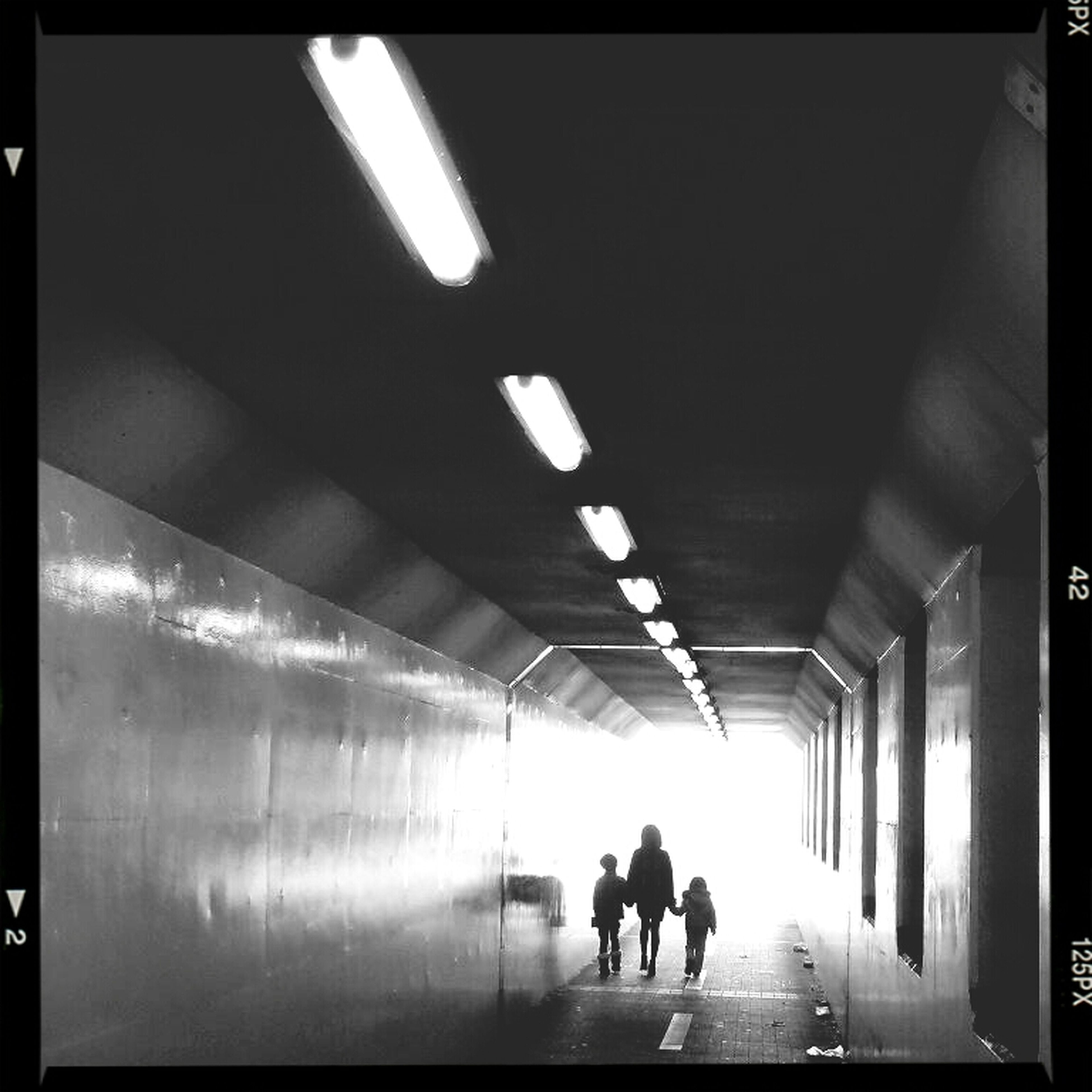 indoors, illuminated, men, walking, lifestyles, ceiling, full length, person, silhouette, the way forward, rear view, built structure, lighting equipment, architecture, leisure activity, subway, transportation