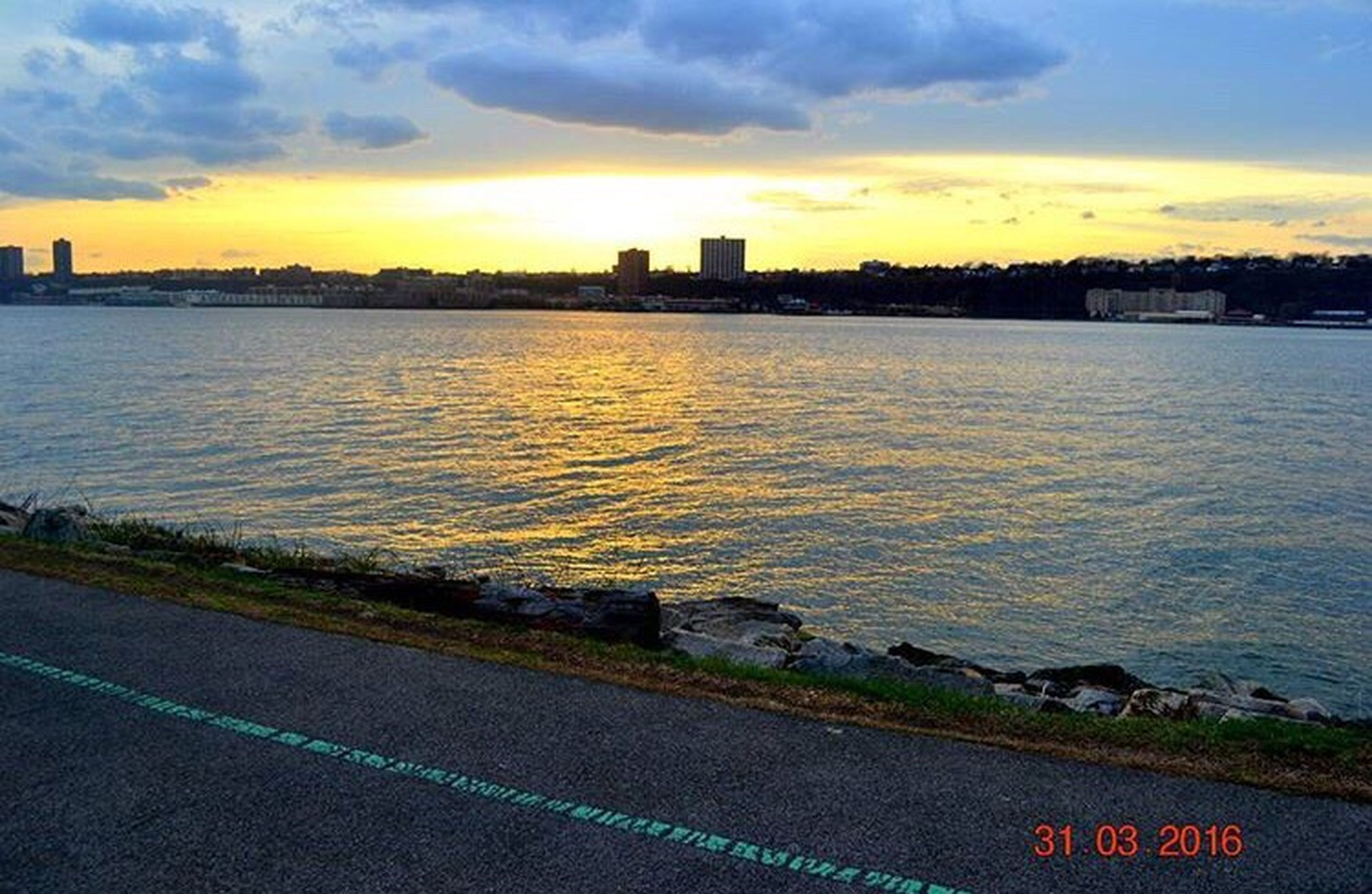 sunset, water, city, building exterior, architecture, scenics, sky, travel destinations, distant, cloud - sky, sea, tranquil scene, river, tranquility, outdoors, nature, calm, blue, beauty in nature, dramatic sky, urban skyline, city life, ocean, tourism, majestic, no people