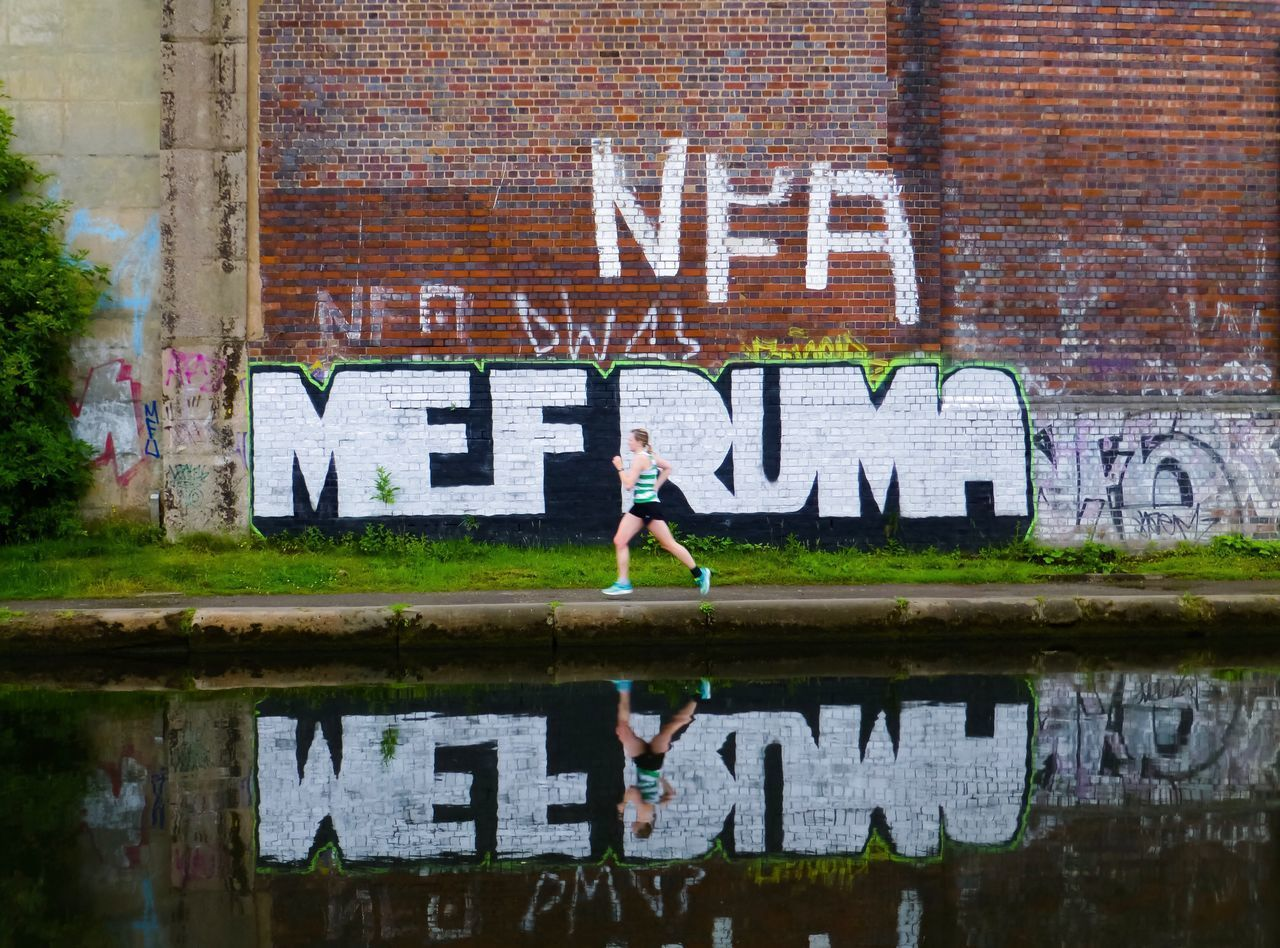 A Lady Runner Running Alongside A Canal In Birmingham Exercising Runner Reflection Canal Running Run Text Day One Person Architecture Full Length Outdoors Real People Built Structure Lifestyles Building Exterior Adult Young Adult People