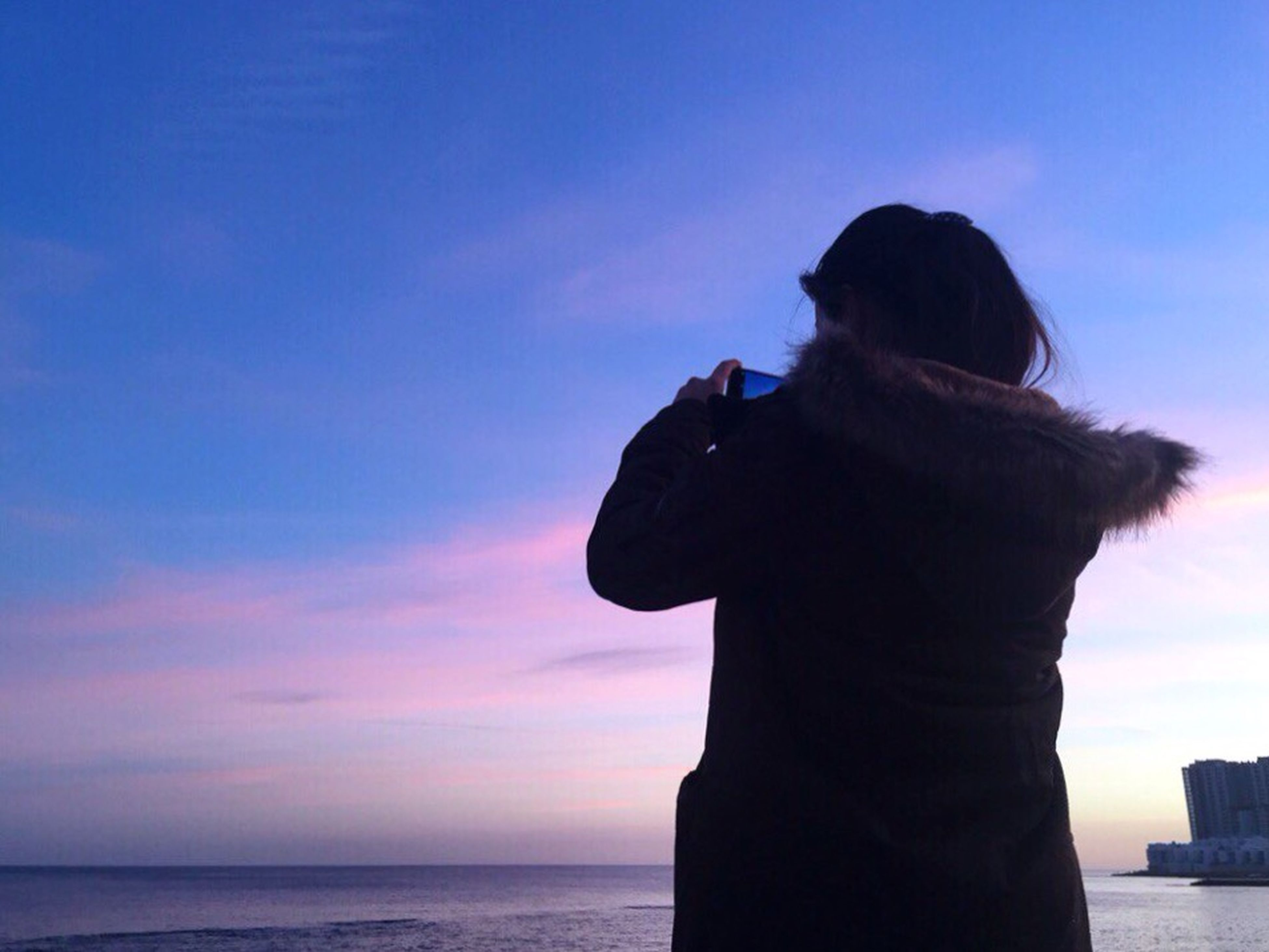 sea, water, horizon over water, sky, sunset, silhouette, tranquility, scenics, tranquil scene, beach, beauty in nature, nature, standing, idyllic, shore, rock - object, sculpture, one person, cloud, cloud - sky
