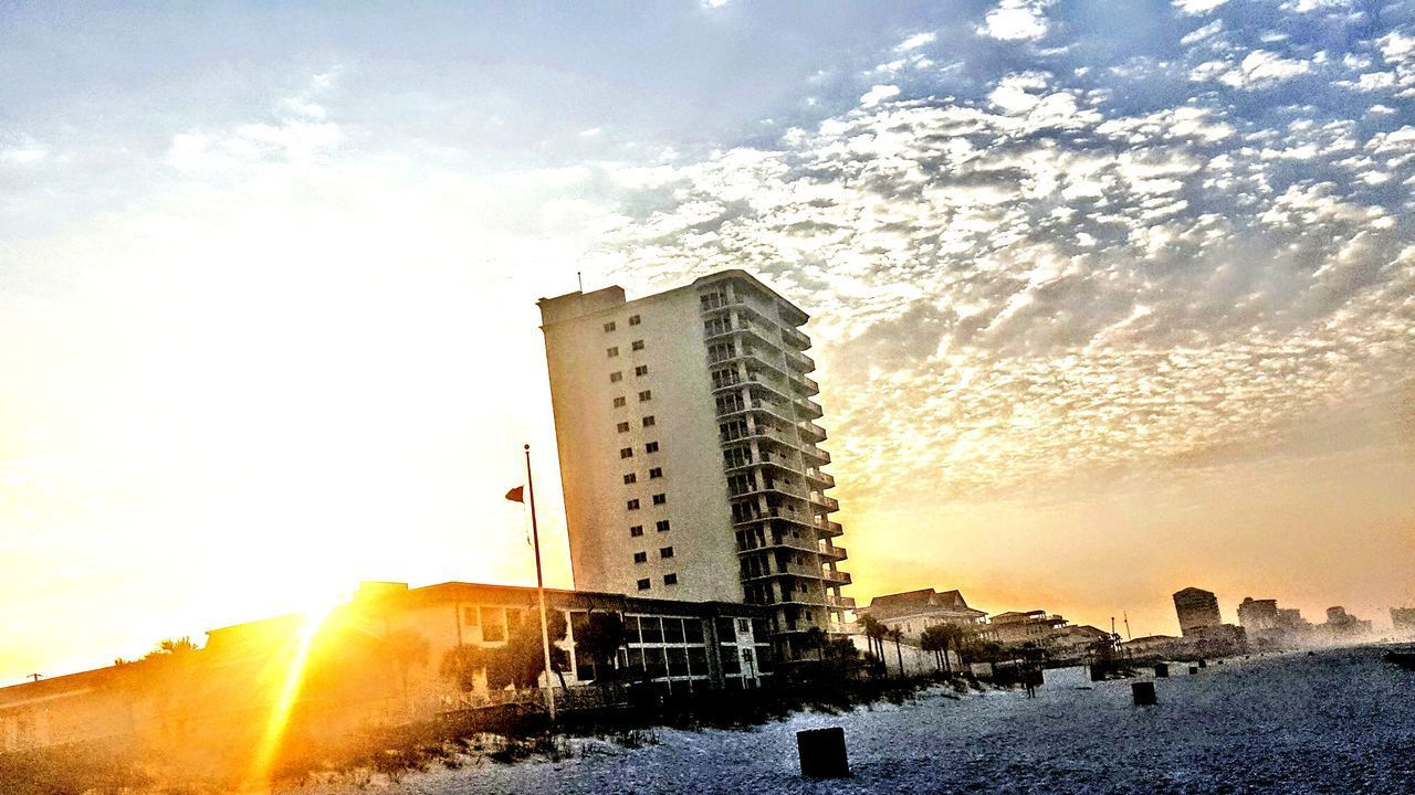 sun, architecture, sunbeam, sky, built structure, building exterior, sunlight, cold temperature, outdoors, sunset, winter, no people, low angle view, cloud - sky, nature, skyscraper, day, snow, water, city, beauty in nature