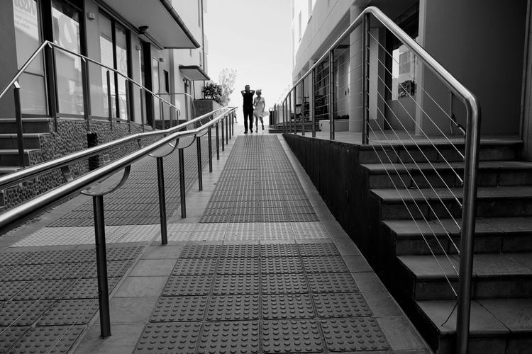 Railing Real People Architecture Built Structure Walking Full Length The Way Forward Men Steps And Staircases Day Lifestyles Women Building Exterior Outdoors Sky Adult People