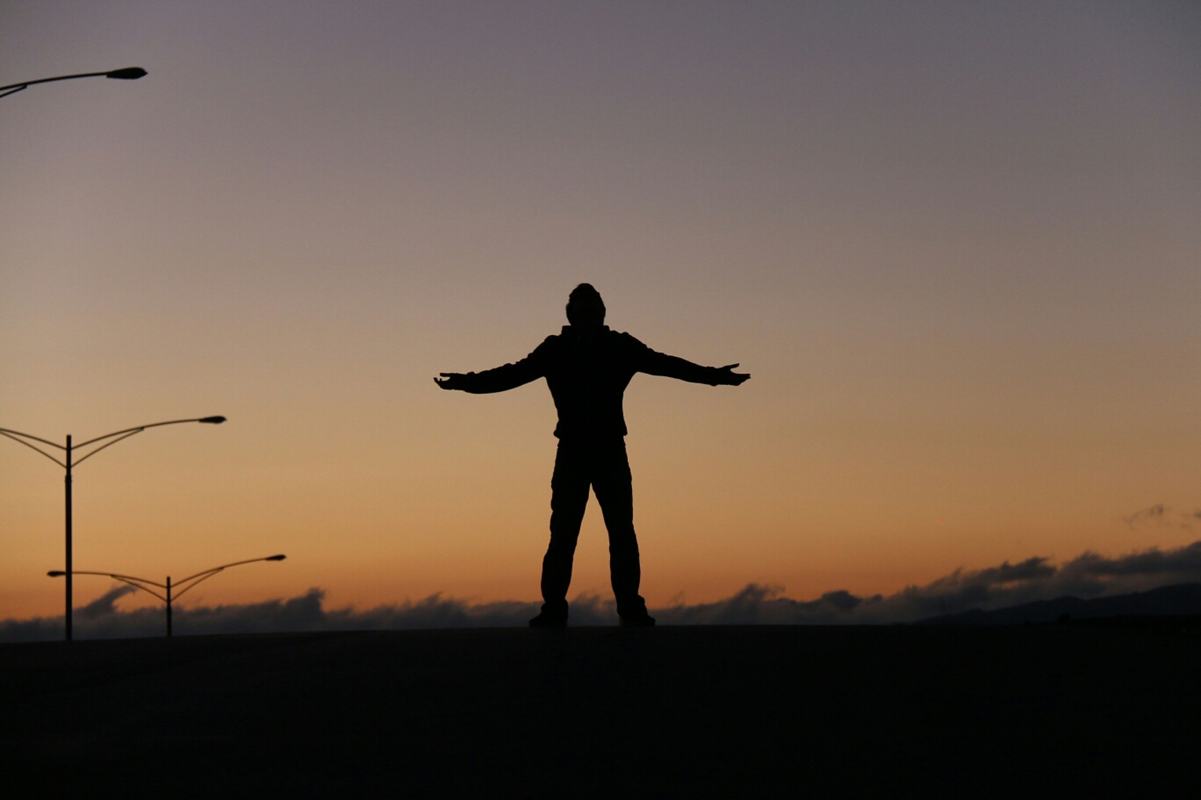 silhouette, full length, sunset, standing, lifestyles, leisure activity, copy space, clear sky, men, arms outstretched, sky, landscape, dusk, tranquility, orange color, tranquil scene, arms raised, nature